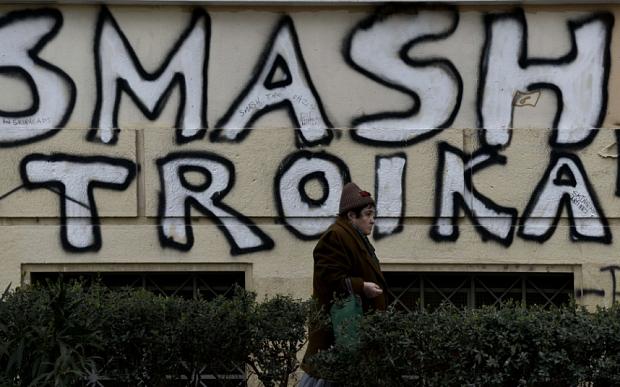 A woman walks past graffiti denouncing t